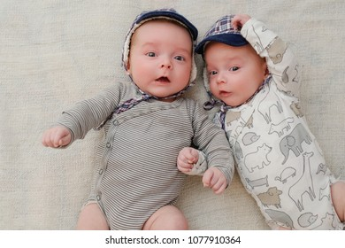Indoor portrait of two cute twin babies, lying down in bed and having fun. High angle shot, view from above. Friendship and brotherhood concept