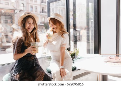Indoor portrait of two stylish sisters relaxing in cafe after shopping. Smiling long-haired girl with glass of juice in hand posing in front of window next to friend in trendy vintage hat.