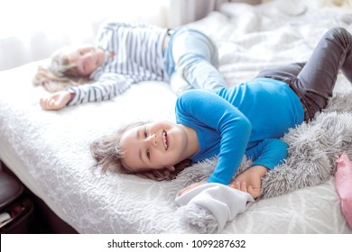 indoor portrait of two young happy girls, sisters, on bed at home, having fun in the morning