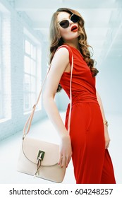 Indoor portrait of young beautiful fashionable woman posing in white interior with small beige shoulder bag. Model wearing stylish sunglasses, elegant red overalls. Waist up. Female fashion concept.