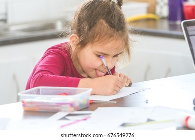 indoor portrait of young creative child girl making art and crafts or writing at home