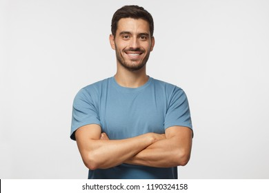 Indoor portrait of young european caucasian man isolated on gray background, standing in blue t-shirt with  crossed arms, smiling and  looking straight at camera