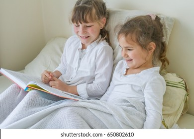 indoor portrait of young european girls - two sisters - lying in bed and reading a book
