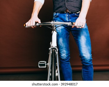 Indoor portrait of young fashion handsome hipster man with vintage bike. Hipster. Warm color. Close up.