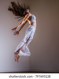 Indoor Portrait of young female middle eastern yogi jumping in the air with hair flying - Shutterstock ID 797693128