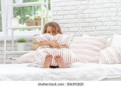 indoor portrait of young happy smiing child girl in her bed, happy morning time