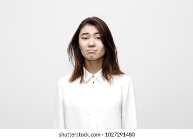 Indoor portrait of young woman dressed in formal white shirt pretending to be offended and very sad. Facial expressions, lifestyle and emotions concept.