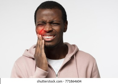 Indoor portrait of young worried African American male isolated on white background dressed in white T-shirt and pink hoodie experiencing strong toothache pressing hand to chin because of sore jaws