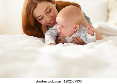 Indoor shot of adorable baby in blue bodysuit trying to crawl along white bed, his red haired mother holding him, looking at him with love, affection and pride. Infancy and childcare. Selective focus