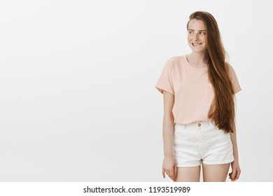Indoor shot of amused attractive female feeling intrigued, having some interesting intention in mind, smirking while gazing left with curiosity, standing over gray background in stylish clothes