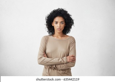 Indoor shot of angry grumpy young mixed race female dressed casually keeping arms folded, looking at camera with strict and skeptical expression, doesn't believe excuses of her unfaithful boyfriend