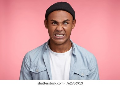 Indoor shot of annoyed mixed race male with sunburnt skin, clenches teeth, frowns face, irritated with friend who is very lazy, isolated over pink background. Furious hipster guy poses in pink studio