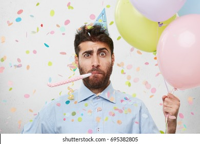 Indoor shot of astonished puzzled guy wearing blue shirt and cone hat on his head looking surprised, holding helium balloons and blowing on party horn. Birthday, celebration and entertainment