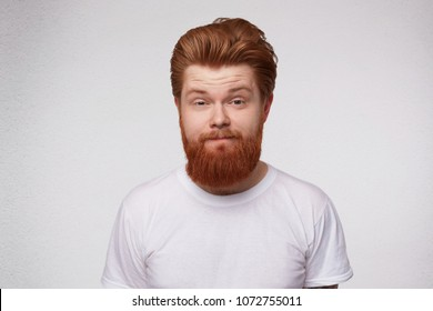 Indoor shot of astonished and shocked redhead unshaved man, curving his lip. Poratrait of young male feels confused. Facial expression