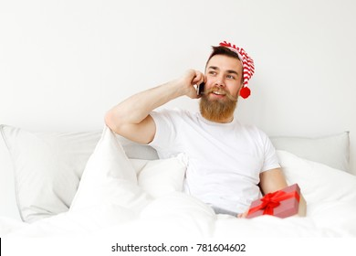 Indoor shot of attractive man with thick long beard and mustache speaks over mobile phone, sits in comfortable bed, prepares wrapped present box for his girlfriend. Holidays, people, technology