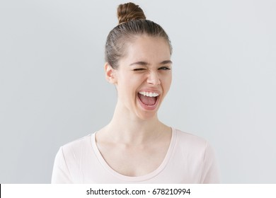 Indoor shot of attractive teenage girl isolated on grey background, looking happy and energetic, smiling with open mouth and winking as if she suggests great ideas for leisure time and activities.
