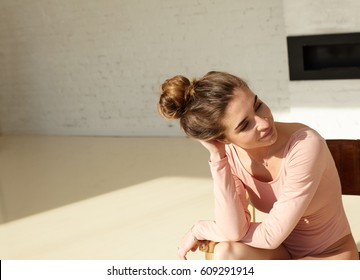 Indoor shot of attractive young Caucasian female with hair bun in tender pink bodysuit smiling timidly, looking to the side with copy space area for your advertising text or promotional content