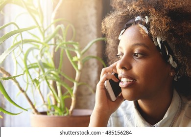 Indoor shot of attractive young dark-skinned woman, using cell phone for ordering pizza for dinner. Serious female having phone talk using electronic device, relaxing at home, looking through window