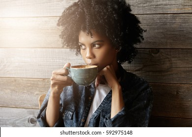 Indoor shot of beautiful African-American woman with Afro hairstyle holding big mug, having fresh cappuccino and enjoying nice view outside window while relaxing alone in modern coffee shop interior