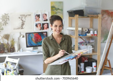 Indoor shot of beautiful brunette female painter wearing shirt, holding paint brush in hands standing near easel, creating masterpiece, smiling pleasantly into camera while being glad to paint
