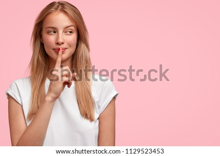 Indoor shot of beautiful female looks mysteriously aside, has intriguing look, asks to be quiet, dressed in casual clothes, stands against pink background with blank copy space for your advertisement