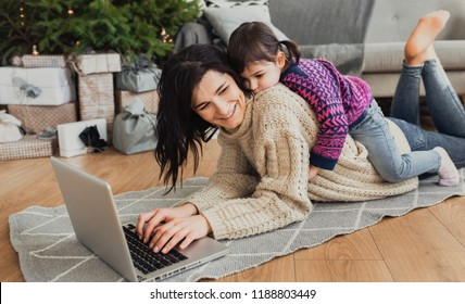 Indoor shot of beautiful happy young woman shopping online on laptop in cozy Christmas interior. Mother lying on the floor next the Christmas tree and sofa and daughter embrace her, shopping gifts.