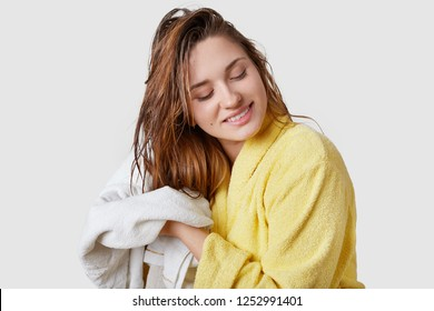 Indoor shot of beautiful woman wipes wet hair with towel, dressed in yellow bathrobe, stands against white background, has pleased facial expression, has shower at home, satisfied with new shampoo