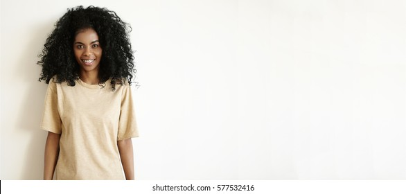 Indoor shot of beautiful young African woman with Afro hairstyle dressed in casual oversize t-shirt smiling joyfully at camera standing at white blank wall with copy space for your advertisement