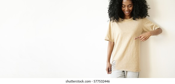 Indoor shot of beautiful young African woman with cute smile looking down and pointing at copy space on her oversize ripped t-shirt. Cheerful dark-skinned girl dressed casually posing at studio wall