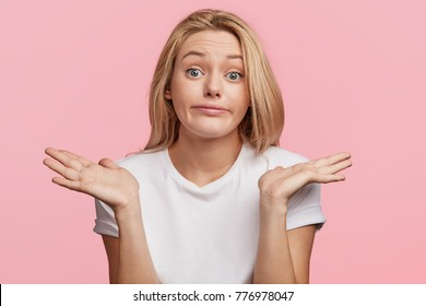 Indoor shot of beautiful young female model shrugs shoulders, has hesitating expression, dressed casually, isolated over pink background. Confused puzzled woman poses indoor, gestures in studio