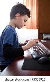 Indoor shot of a boy typing on a keyboard
