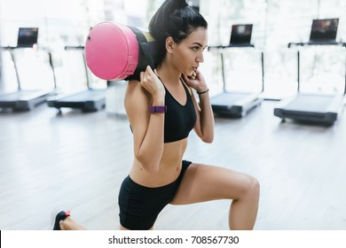 Indoor shot of brunette sporty woman working out with sandbag while exercise for butt legs in fitness club or gym. Attractive athletic female doing hard workout with weight training with copy space.