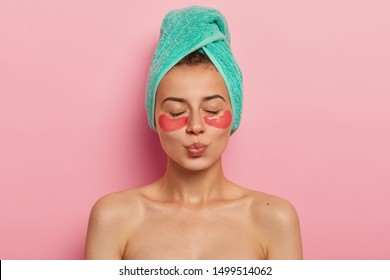 Indoor shot of calm relaxed woman has fresh healthy skin, keeps eyes shut, wears collagen patches under eyes, wears turquoise towel on head, keeps lips rounded, gets facial treatment in spa salon