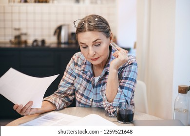 Indoor shot of casually dressed sixty year old woman pensioner studying Spanish by herself, learning new words, sitting with copybook at kitchen table using laptop, having serious focused look