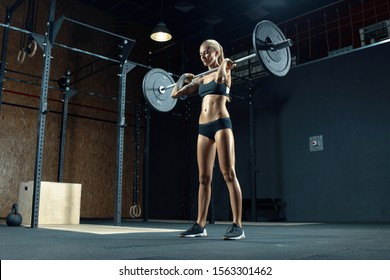 Indoor shot of caucasian female performing deadlift exercise with barbell Confident young blonde woman doing workout in gym. Female performing deadlift exercise with weight bar Concept photo.