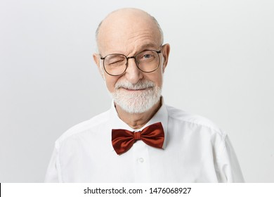 Indoor shot of charismatic charming senior European man wearing elegant red bow tie and eyeglasses having playful facial expression, winking at camera with smile. Body language and human emotions