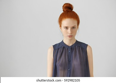 7b0145642 Indoor shot of charming young lady of European appearance wearing ginger  hair in bun, posing
