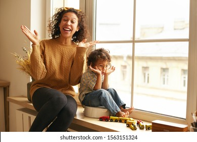 Indoor shot of cheerful charming young mother and cute barefooted little son sitting together on windowsill on rainy day, playing seek and hide, singing and dancing, having happy overjoyed looks