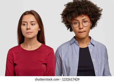 Indoor shot of contemplative mixed race women purse lips, being deep in thoughts, have sad expressions, dressed in casual clothes, isolated over white background. Facial expressions concept.
