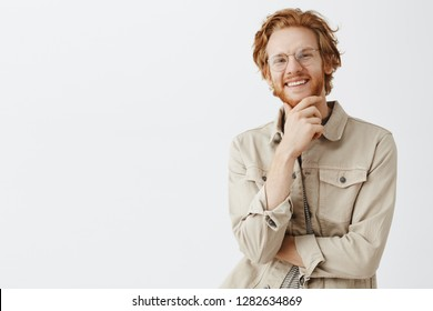 Indoor shot of creative artistic and cute redhead guy in transparent glasses rubbing beard and smiling with pleased curious expression having interesting thought or idea over gray background