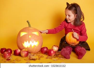 Indoor shot of cute dark haired girl sitting on floor over backgroundof autumn scenery in studio. Autumn harvest - pumpkin, apples. Little kid playing with Jack o'Lantern. Halooween concept.
