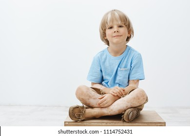 Indoor shot of cute happy blond child with positive smile sitting with crossed hands, having vitiligo, smiling broadly while hanging out with pals in kindergarten, having fun over gray background