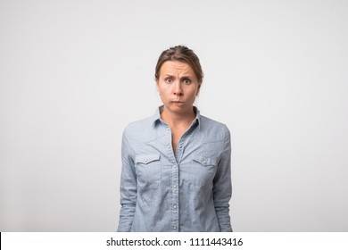 Indoor shot of cute woman in denim shirt in denim shirt having doubtful and indecisive face expression, pursuing her lips as if forbidden to say anything. Confused young female emotion concept