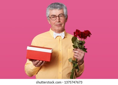 Indoor shot of elderly gentleman with serious facial expression holds gift box and red roses, dressed in yellow shirt with bowtie and glasses, being late for birhday party, has white hair and wrinkles