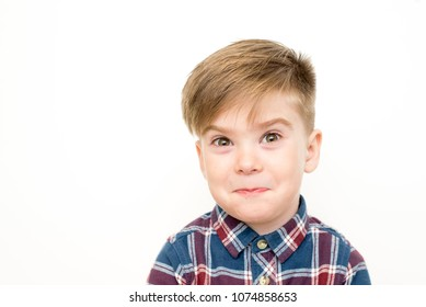 indoor shot of emotional young boy in color shirt grimacing, bugging eyes out, making goofy faces, twisting lips, looking at camera with crazy and stupid expression on his face