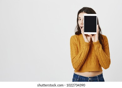 Indoor shot of excited and happy woman hiding face behind tablet as if promoting it, peeking and expressing amazement over gray background. Girl finally found great present for mother