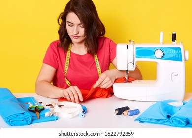 Indoor shot f concentraed woman dressmaker sewing in her studio, sitting with opened mouth, ready to sew buttons, has confident facial expression, isolated over yellow studio wall. Sewing concept.