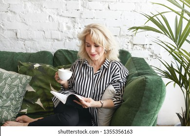 Indoor shot of fashionable attractive senior blonde female in striped shirt relaxing on comfortable couch with magazine and cup of tea or coffee, having joyful expression, focused on reading