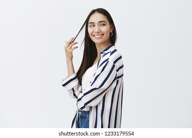 Indoor shot of feminine flirty fashionable woman in striped blouse, turning right while playing with hair strand and smiling joyfully, being satisfied with finished design project over gray background
