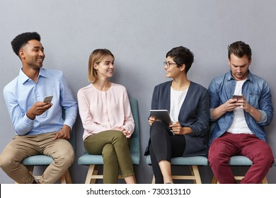 Indoor shot of four not acquainted young people have lively conversation, come on appointment, sit in waiting room, use modern gadgets not to feel bored, speak with each other, have good mood